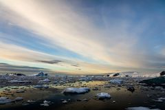Icebergs floating in the ocean against a dramatic blue and cloudy sky, Antarctica Royalty Free Stock Photos