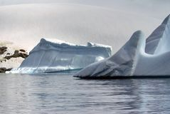 Icebergs floating in the seas of Antarctica. Icebergs floating in an Antarctic sea, under overcast skies, with a snow covered slope in the background Stock Photos