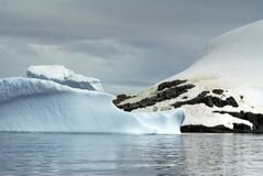Icebergs floating in the seas of Antarctica. Icebergs floating in an Antarctic sea, under overcast skies, with a snow covered slope to the side Stock Image