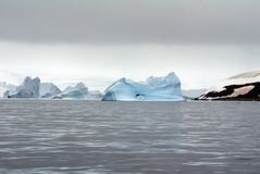 Icebergs floating in the seas of Antarctica. Icebergs floating in an Antarctic sea, under overcast skies Royalty Free Stock Photography