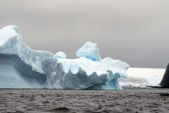 Icebergs floating in the seas of Antarctica. Icebergs floating in an Antarctic sea, under overcast skies Royalty Free Stock Photos