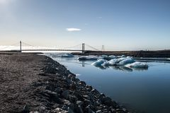 Icebergs floating under a bridge. Icebergs floating under the bridge over the river from the Jökulsárlón Glacier Lagoon to the ocean, Iceland stock images