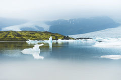 Icebergs in the glacial lake with mountain views. Stock Image