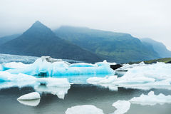 Icebergs in the glacial lake with mountain views. Stock Photo