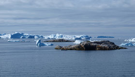 Icebergs,  Greenland west coast in summer. Icebergs west of Ilulissat town, with a small fishing boat next to an island Royalty Free Stock Images