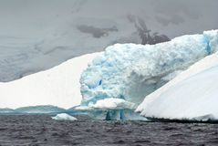 Icebergs in the frigid waters of Antarctica, in front of a mountain. Icebergs grounded in a bay in the frigid waters of Antarctica, with a mist covered mountain stock photography