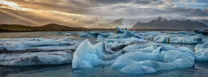 Icebergs in Iceland`s Jökulsarlon Glacial Lagoon at Sunset. The Battlegrounds of Climate Change take form as Bright Blue Icebergs break away at Record Pace at Stock Photography