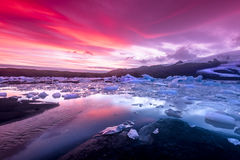 Icebergs in Jokulsarlon glacial lagoon. During a vibrant red sunset rests motionless as it is framed by cold ocean water Stock Images