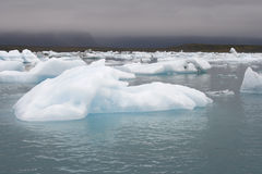 Icebergs in lake with moody sky Royalty Free Stock Photos