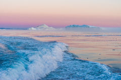 Icebergs in the midnight sun, Ilulissat, Greenland. Huge stranded icebergs at the mouth of the Icejord near Ilulissat at midnight, Greenland Royalty Free Stock Images