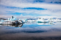Icebergs are reflected in mirrored water of the ocean Stock Image