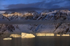 Icebergs in Scoresbysund - Greenland. Late afternoon sun on icebergs and mountains in Scoresbysund on the east coast of Greenland Stock Photography