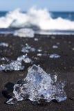 Icebergs se cassant sur la plage noire de sable en Islande image stock