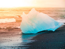 Icebergs sphashed by sea waves on black beach at sunrise time near Jokulsarlon glacier lake, Iceland Stock Photography