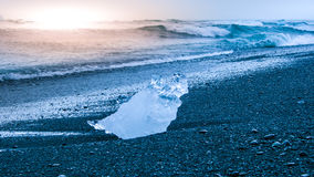 Icebergs sphashed by sea waves on black beach at sunrise time near Jokulsarlon glacier lake, Iceland Stock Photo