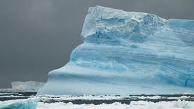 Icebergs and Storms. A beautiful, blue iceberg against gray storm clouds - Antarctic Stock Photo