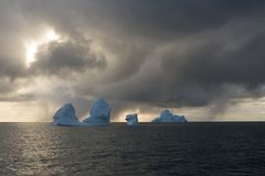 Icebergs and sun behind the snow clouds Royalty Free Stock Photos