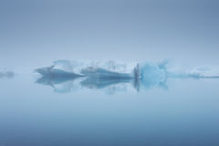 Icebergs and their reflections in a fog, Jokulsarlon, Iceland Stock Photo