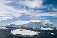 Icebergs Under a Blue Sky. A large iceberg and many smaller ones under blue skies - Antarctic Stock Photos