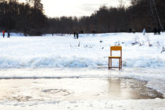 Icebound chair near opening water in frozen lake Stock Images