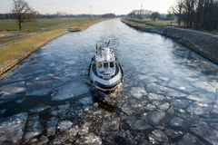Icebreaker. In Dutch canal breaks the ice in pieces Stock Photo