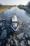 Icebreaker. In Dutch canal breaks the ice in pieces Stock Image