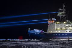 Icebreaker research vessel on research site. Icebreaker research vessel near a research site marked with safety flags searching by strong projectors Stock Photography