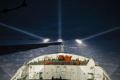 Icebreaker  ship cruising at night in the polar seas. Icebreaker ship cruising at night by the aid of night-piercing projectors in the polar sea Royalty Free Stock Images