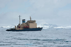 Icebreaker which floats on the frozen Strait spring Antarctic mo Stock Image