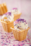 Icecream. Delicious cone with vanilla icecream topped with lilac sprinkles Stock Photography