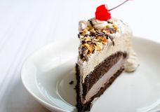 Icecream cake with red cherry on white plate Stock Photography