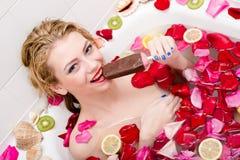 Icecream i brunnsort: den härliga unga frestande kvinnan som äter glass i bad med rosa kronblad och frukt, skivar lyckligt le Royaltyfri Fotografi