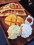 Icecream with mango. A delicious dessert, vanilla ice cream with mango, waffles and orange sauce Stock Images