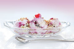 Icecream Sundae. Berry Icecream with strawberry topping, chopped nuts and a cherry, in glass dish with parfait spoon. Natural light reflected on shiny white royalty free stock photos