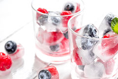 Icecubes with blueberry and raspberry in glass on wooden table Royalty Free Stock Photos