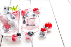 Icecubes with blueberry and raspberry in glass on wooden table Stock Images