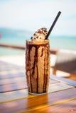 Iced смешал frappucino молока и шоколада с взбитой сливк на пляже Стоковое Фото