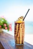 Iced смешал frappucino молока и шоколада с взбитой сливк на пляже Стоковое Изображение