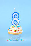 Iced birthday cupcake with with lit number 8 candle Stock Images