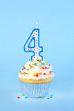 Iced birthday cupcake with with lit number 4 candle Royalty Free Stock Photos