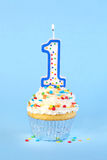 Iced birthday cupcake with with lit number 1 candle Stock Images