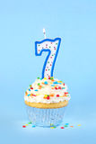 Iced birthday cupcake with with lit number 7 candle Royalty Free Stock Photography