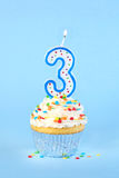 Iced birthday cupcake with with lit number 3 candle Stock Image