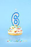 Iced birthday cupcake with with lit number 6 candle. And sprinkles royalty free stock image