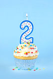 Iced birthday cupcake with with lit number 2 candle Stock Photo