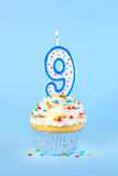 Iced birthday cupcake with with lit number 9 candle Stock Photography