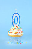 Iced birthday cupcake with with lit number 0 candle Stock Photos
