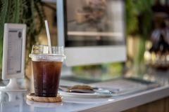 Iced black americano coffee with cookie. Iced black coffee & x28;americano& x29; with cookie on table with PC computer in modern coffee shop stock photography