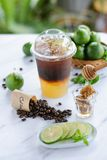 Iced black coffee with honey and fresh green lime royalty free stock image