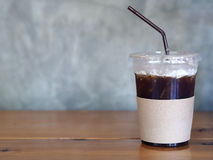 Iced Black Coffee in plastic cup on wooden table. Iced Black Coffee in plastic cup on wooden table Royalty Free Stock Photography
